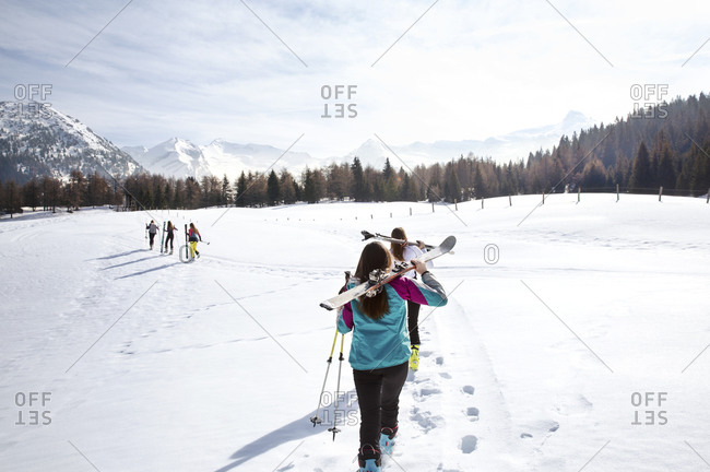 Five teenage girl skiers carrying skis in snow covered landscape, rear view, Tyrol, Styria, Austria