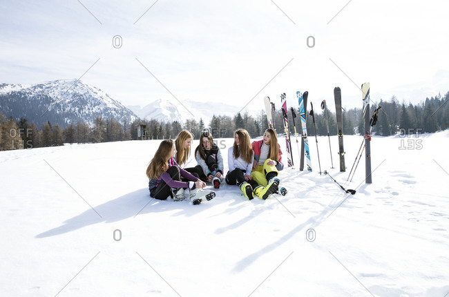 Five teenage girl skiers sitting in snow covered landscape, Tyrol, Styria, Austria
