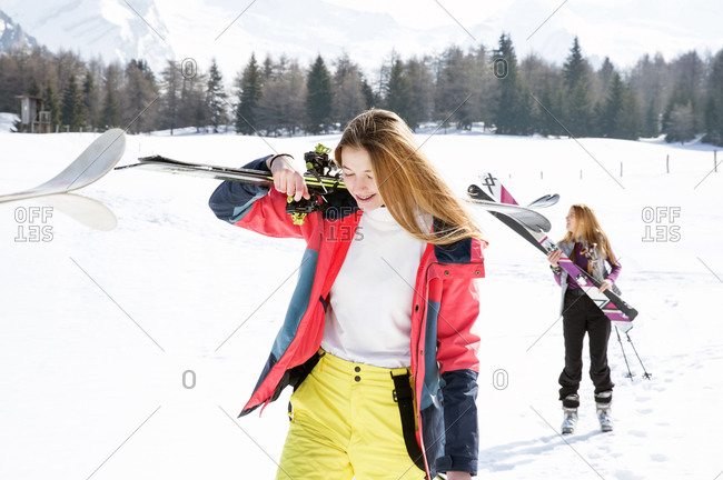 Two teenage girl skiers walking in snow covered landscape,  Tyrol, Styria, Austria