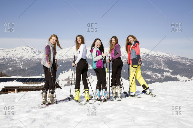 Five teenage girl skiers looking over their shoulder in snow covered landscape, portrait, Tyrol, Styria, Austria