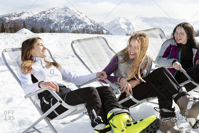Three teenage girl skiers sitting in deck chairs in snow covered landscape, Tyrol, Styria, Austria