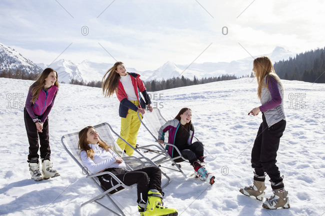 Five teenage girl skiers standing and in deck chairs in snow covered landscape, Tyrol, Styria, Austria