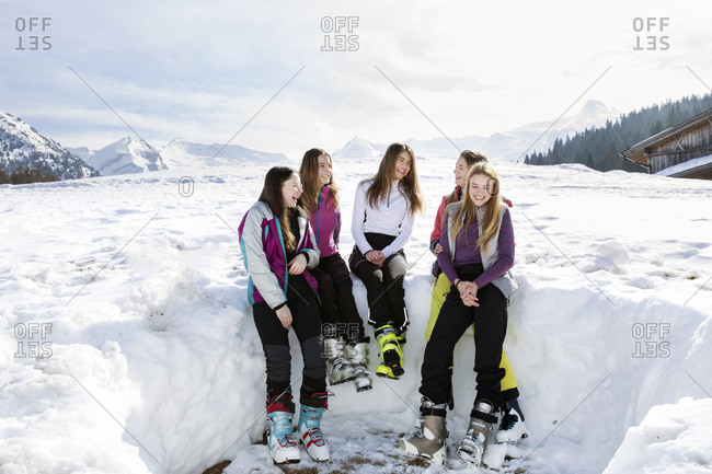 Five teenage girl skiers sitting laughing in snow covered landscape, Tyrol, Styria, Austria