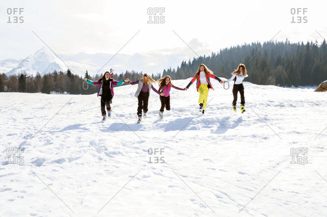 Five teenage girl skiers running and laughing in snow covered landscape, Tyrol, Styria, Austria