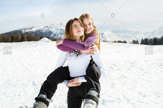 Teenage girl skier getting piggyback from best friend in snow covered landscape, portrait, Tyrol, Styria, Austria