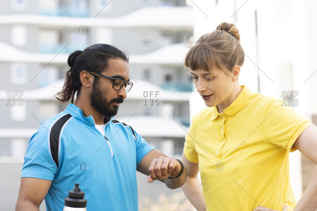 Multi-ethnic couple checking time after exercise
