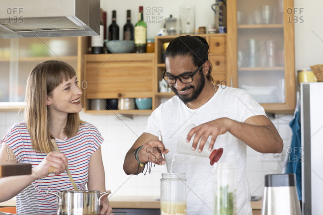 Multi-ethnic couple talking and cooking in kitchen