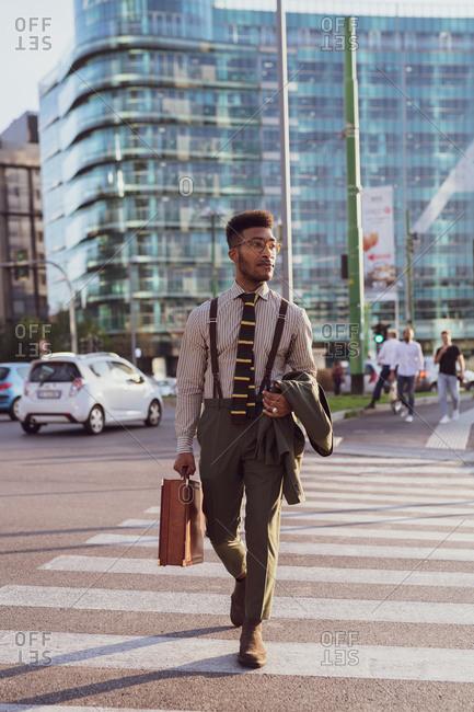 Businessman walking on pedestrian crossing, Milano, Lombardia, Italy