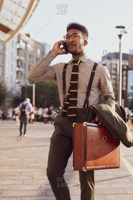 Businessman using smartphone on pavement, Milano, Lombardia, Italy