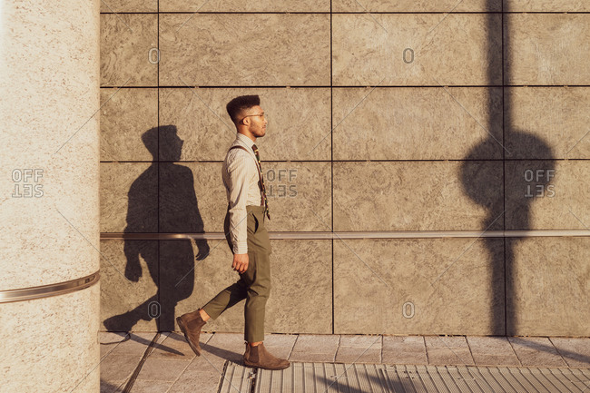 Businessman walking past concrete wall, Milano, Lombardia, Italy