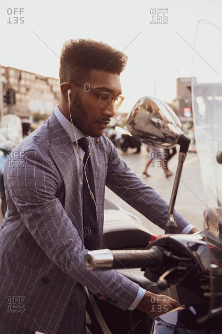 Businessman starting motorcycle on pavement