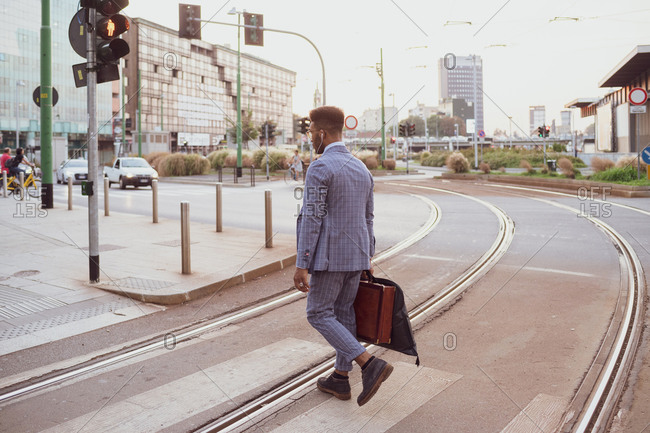 Businessman crossing tram line, Milano, Lombardia, Italy