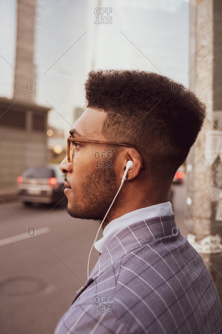 Businessman with earphones on pavement
