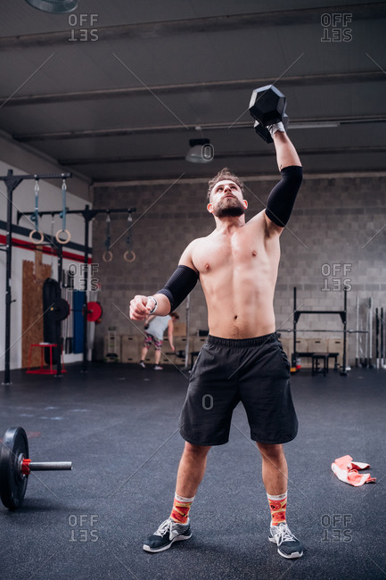 Bare chested young man training, lifting dumbbell in gym