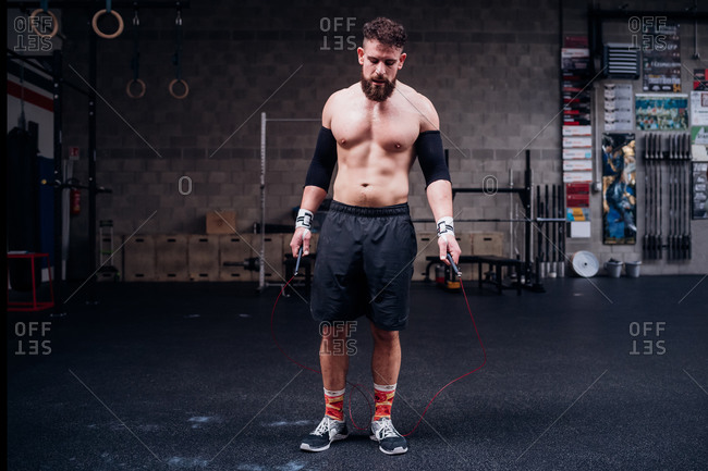 Bare chested young man training, holding skipping rope in gym