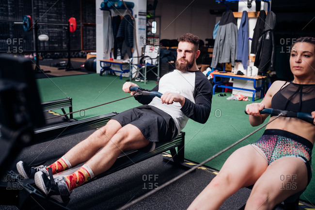 Young woman and man training on rowing machines together in gym