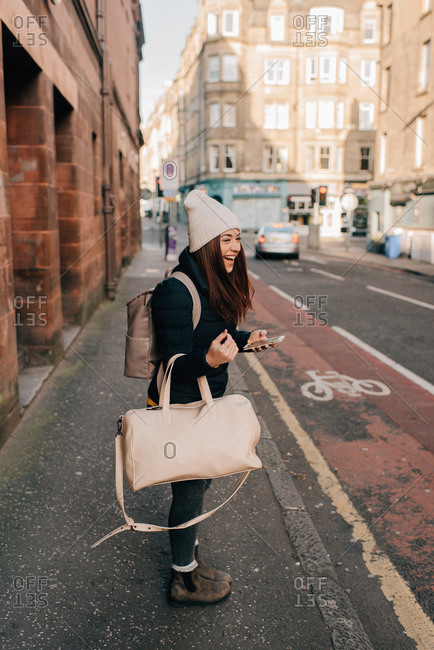 Woman waiting on curb with cellphone and luggage, Edinburgh, Scotland