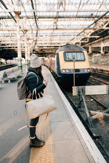 Woman waiting on platform in train station, Edinburgh, Scotland