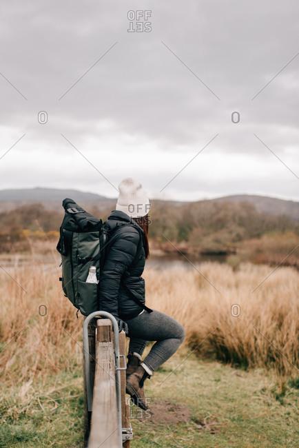 Trekker sitting on fence by Loch Lomond, Trossachs National Park, Canada