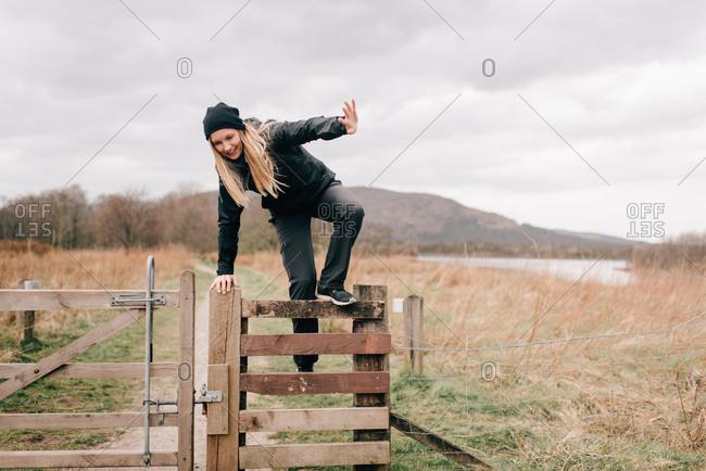 Trekker climbing over fence by Loch Lomond, Trossachs National Park, Canada