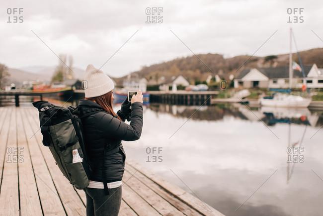 Trekker photographing Loch Lomond, Trossachs National Park, Canada