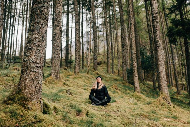 Trekker meditating in forest, Trossachs National Park, Canada