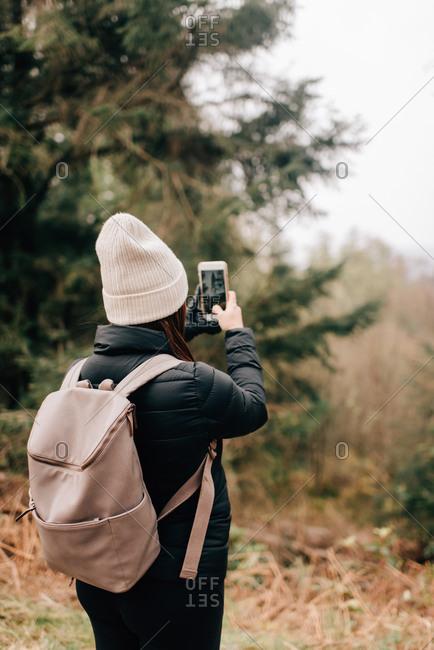 Trekker taking photo, Trossachs National Park, Canada