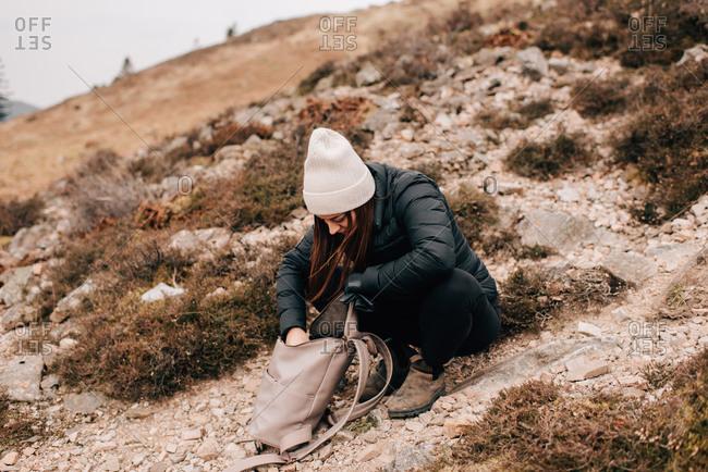 Trekker searching in bag, Trossachs National Park, Canada