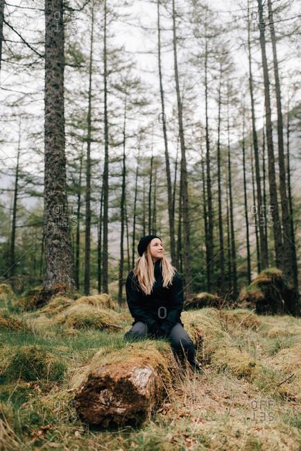 Woman sitting on log, Trossachs National Park, Canada