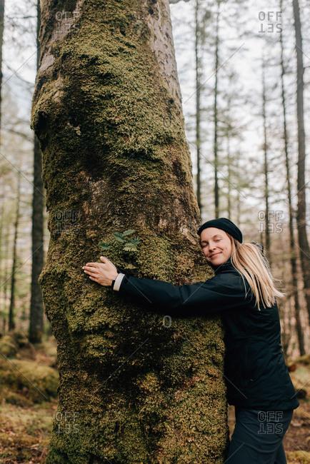 Woman hugging tree, Trossachs National Park, Canada