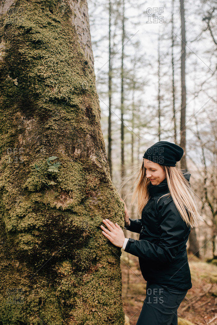 Woman touching tree, Trossachs National Park, Canada