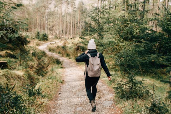 Woman walking through forest, Trossachs National Park, Canada