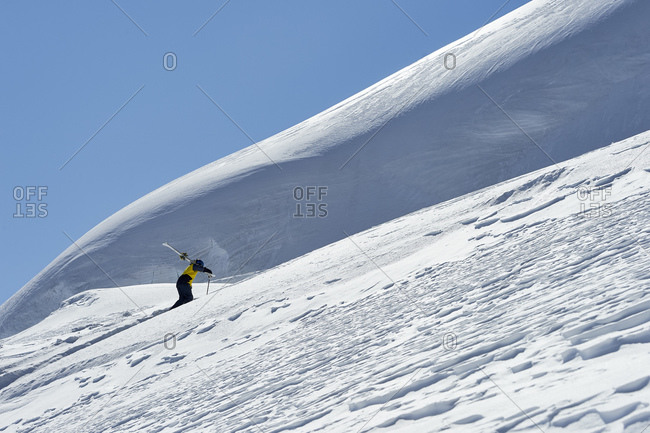 Skier walking up mountain, Saas-Fee, Valais, Switzerland