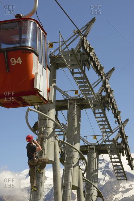 Maintenance worker climbing up cable car, Saas-Fee, Valais, Switzerland