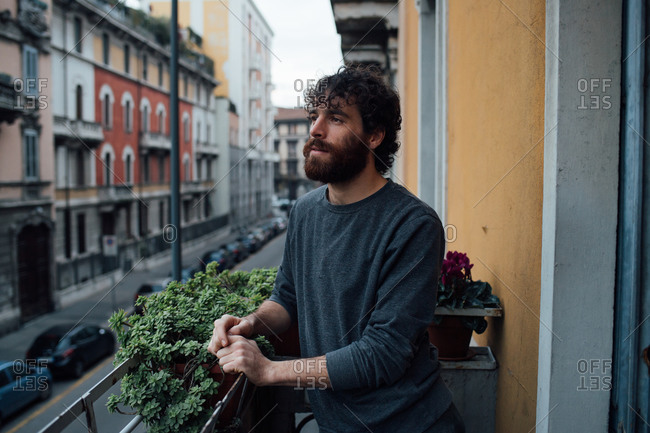 Bearded young man in deep thought on balcony