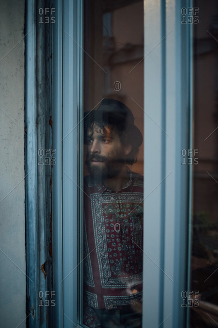 Bearded young man in deep thought by window