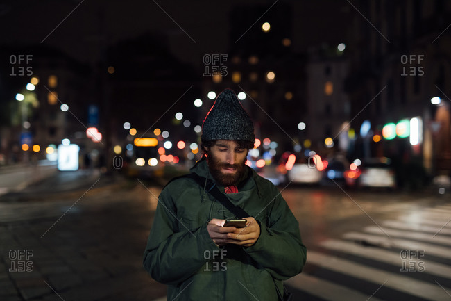 Bearded young man using smartphone on street