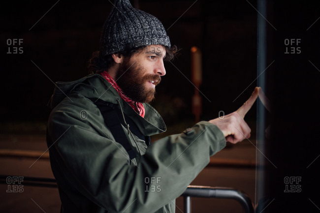 Bearded young man loitering on street