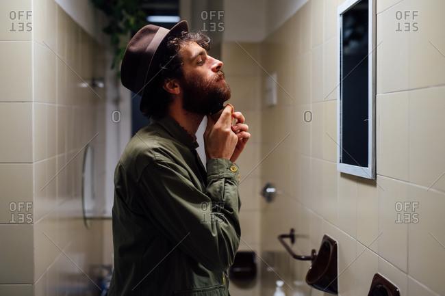 Bearded young man brushing beard in bathroom