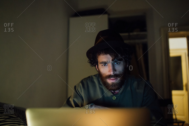 Bearded young man using laptop at home