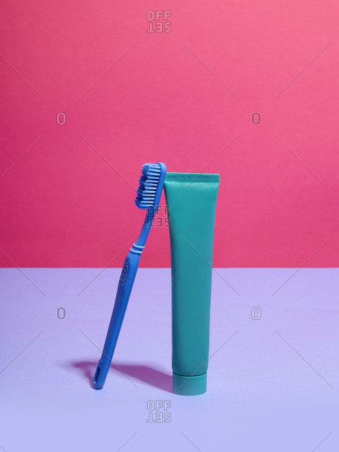 Toothbrush and toothpaste against pink and lilac background