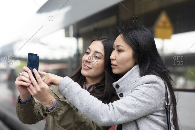 Friends reading text message on smartphone in street