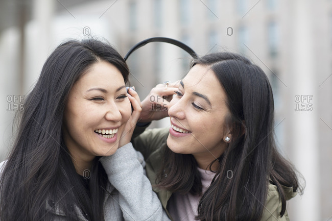 Friends sharing headphone, listening to music in city