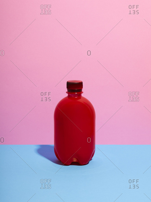 Still life with red plastic bottle and pink background