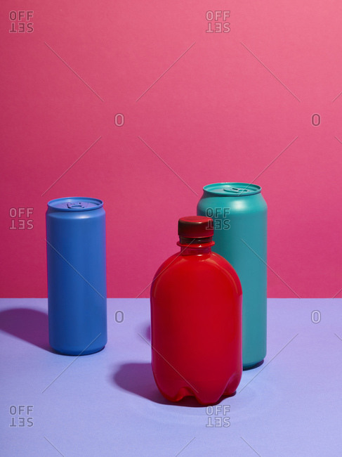 Still life of turquoise and blue drink cans with red bottle and pink background