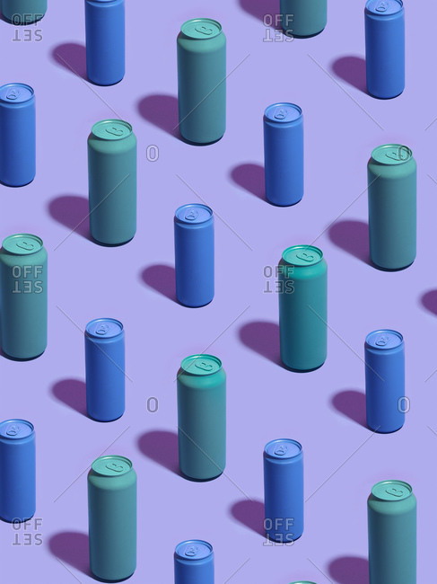 Still life of turquoise and blue drink cans in diagonal rows on purple background
