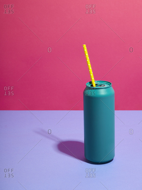 Still life of turquoise drink can with yellow straw and pink background