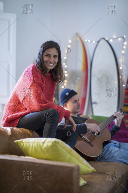 Young woman sitting up on living room sofa with young man playing guitar