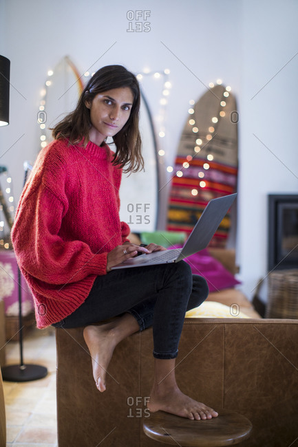 Young woman in red sweater on living room sofa using laptop, portrait
