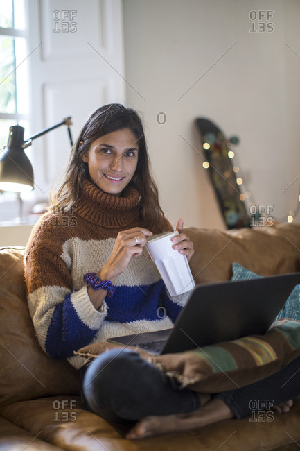Young woman in knit sweater relaxing on living room sofa with laptop and drink, portrait